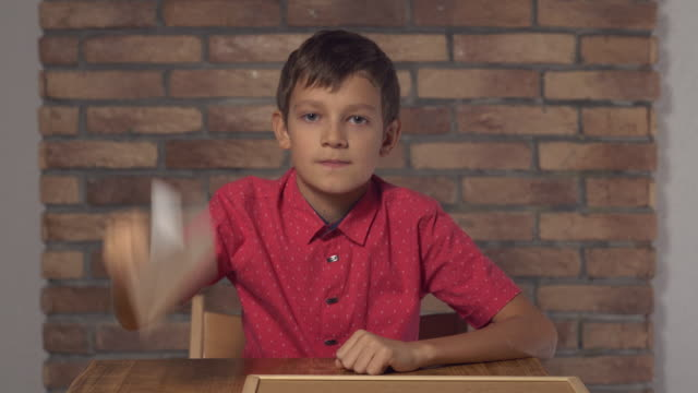 child sitting at the desk holding flipchart with lettering travel on the background red brick wall video