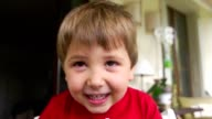 Child smiling and squinting to camera video