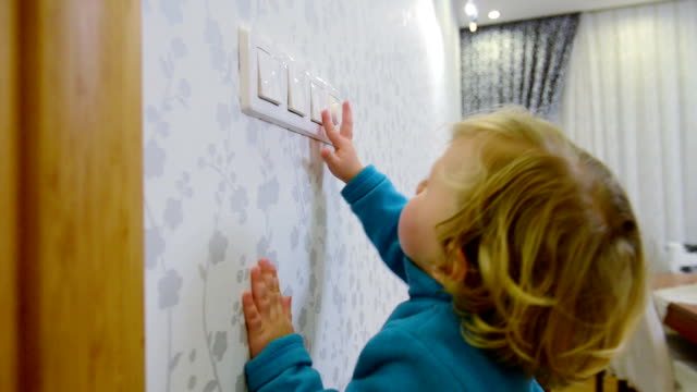 DOLLY: Child switching off a light switch video