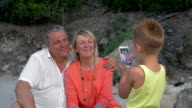 Child taking picture of grandparents with cell phone video