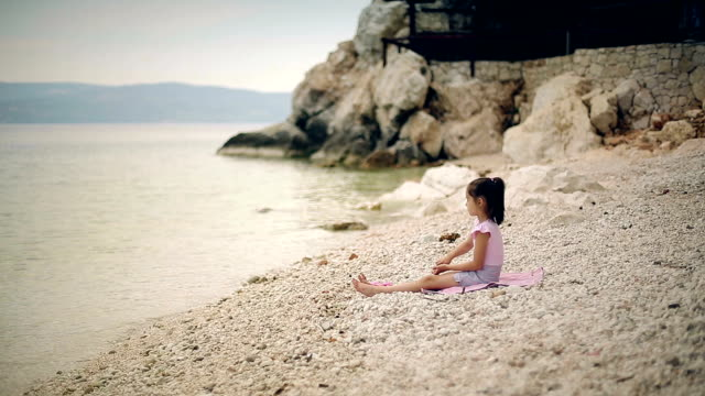 Child throwing stones into the water. video