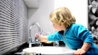 DOLLY: Child turning off a faucet video