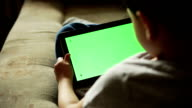 Child using a digital tablet PC with green screen video