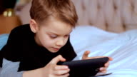Child using digital tablet alone at home, playing game video