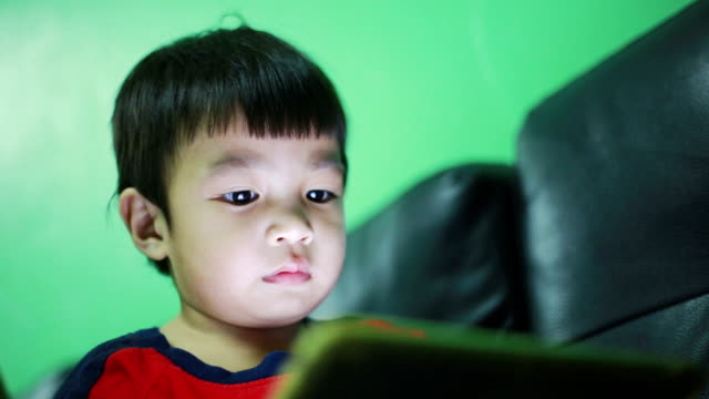 Child using digital tablet alone at home video
