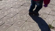 A child walks along the path. The path is covered with diamond-shaped tiles. video