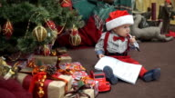 A child with a letter to santa chews pen and smiling video