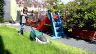 child with lawnmower working in the garden video