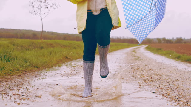 SLO MO Child with umbrella skipping through a puddle video