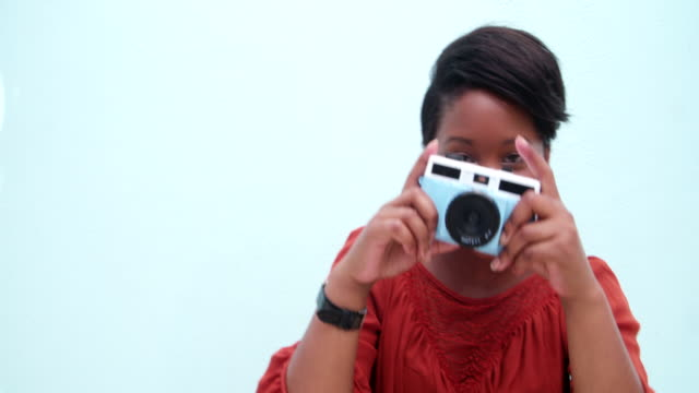 Childish young african woman taking a photo with vintage camera video