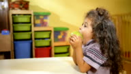 Children and healthy food, baby girl eating fruit at school video