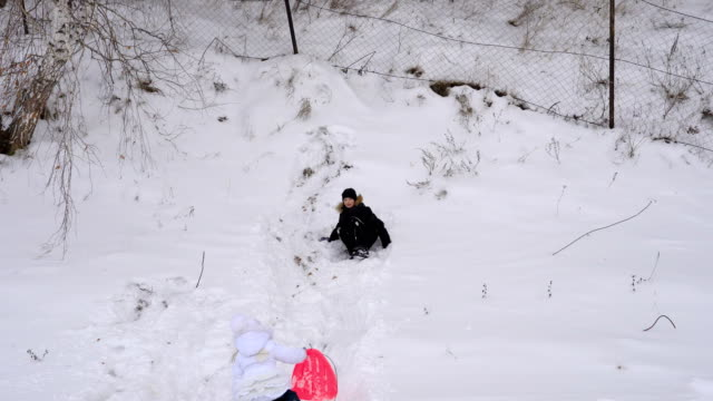 Children are trying to ride on the hillside. Boy and girl roll down the hill. Winter fun for children in the park. A cloudy winter day. video