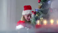 Children at home decorating Christmas tree view through the window video