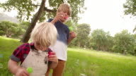 Children blowing bubbles at park in slow motion video