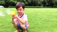 Children blowing bubbles in slow motion video