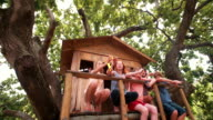 Children blowing bubbles on the porch of a wooden treehouse video