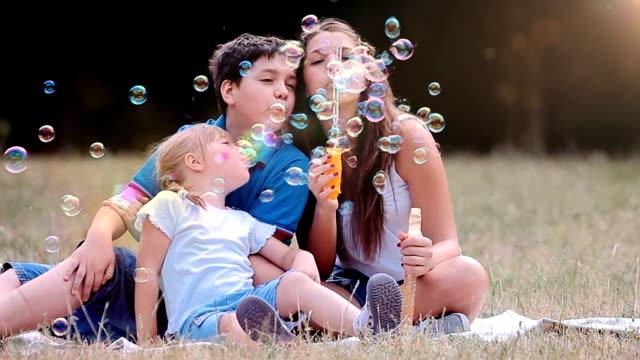 Children blowing bubbles video