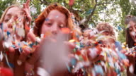 Children blowing colorful paper confetti outdoors in a park video