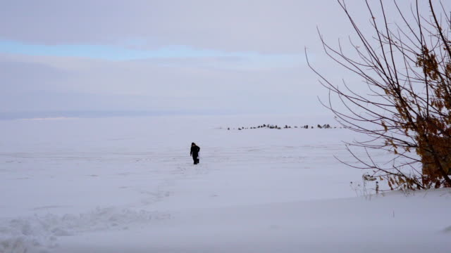 Children come back from the lake covered with ice. Boy and girl walked across the ice of a large lake. The lake is covered with lots of snow. A cloudy winter day. video