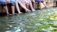 Children dabbling legs in river video