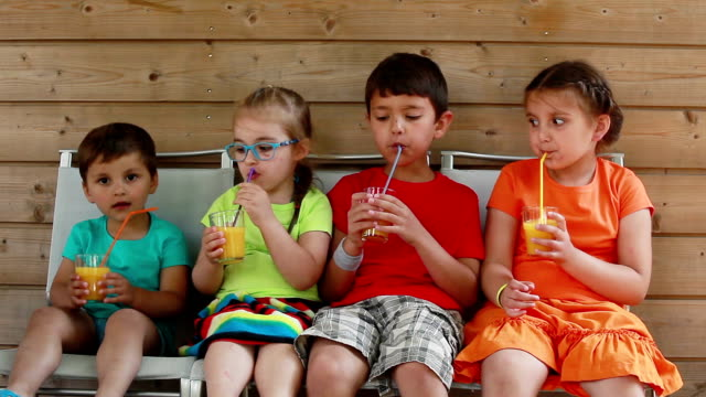 children drink orange juice while sitting on chairs video
