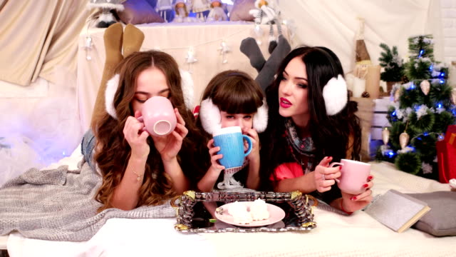 children drink tea, three sisters different ages spend time together, talking, laughing, enjoying a warm drink, a cozy atmosphere in the house video