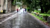Children go in the rain, defocused, sidewalk, day video