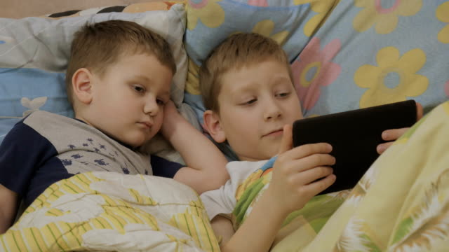 children in bed use tablet and wave hands video