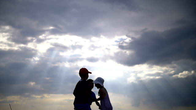 children jumping holding hands on a background of clouds at sunset video