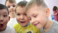 Children look at the camera happy in kindergarten. true emotions video