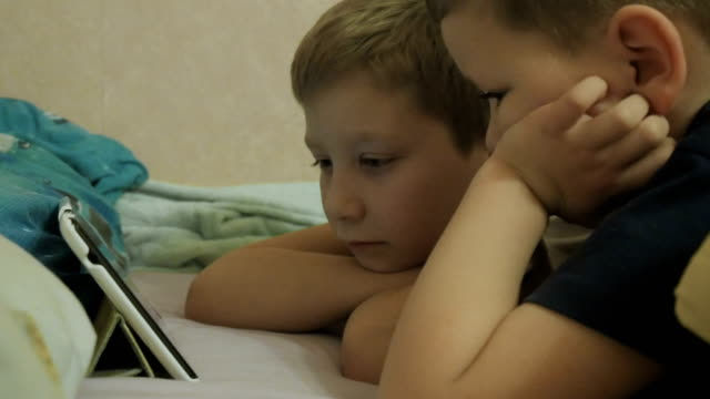 children lying on a bed and watching the show video