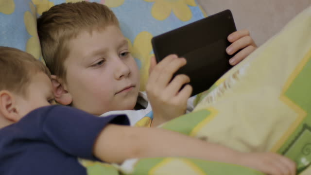 children on bed with online device video