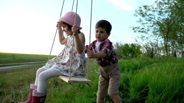 Children on Swing, Two kid ride, Slow Motion, Siblings swinging together, Young little child girl and boy spinning in tree swing video