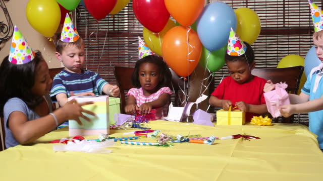 Children opening presents at birthday party video