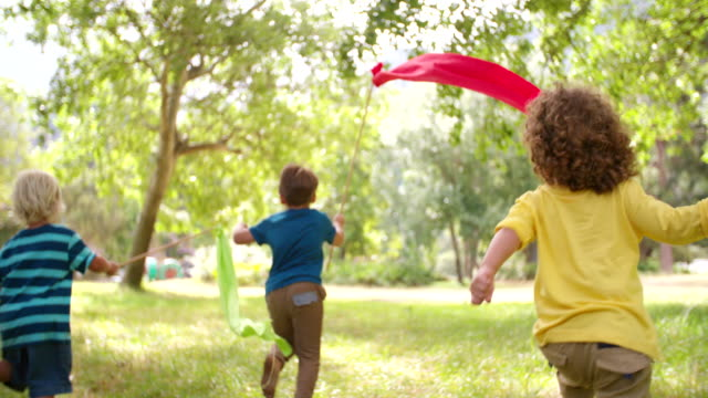 Children playing and running in a park with colourful banners video