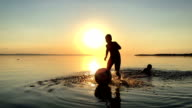 Children playing ball in the water at sunset. video