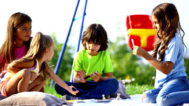 Children playing board game outdoors. video