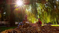 Children playing in fall leaves, slow motion video