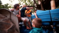 Children playing on a tractor on a summer day video