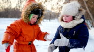 children playing outdoors in winter. The child builds a wall of snow stones video