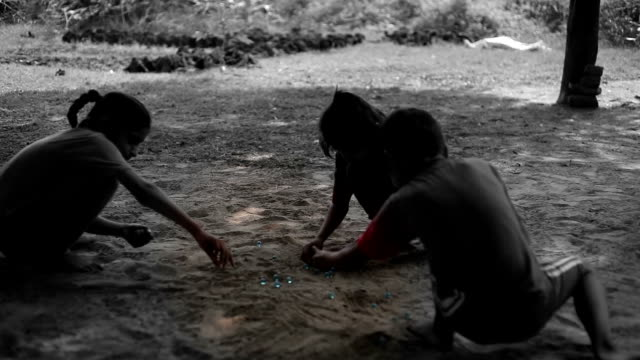 Children playing taw outdoor in the nature video