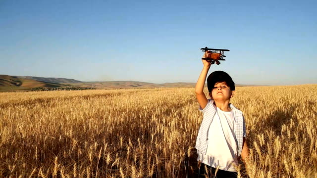 SLO MO Children playing with airplane in the field video
