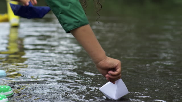 Children Playing with Paper Boats in Puddle video