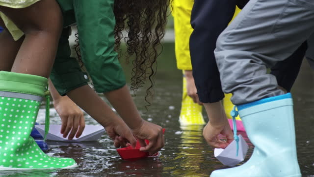 Children Putting Paper Boats in Puddle video