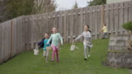 Children running through yard while searching for Easter eggs video