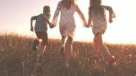 Children running with mother in nature, enjoying summer sunset video