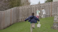 Children searching yard for Easter eggs video