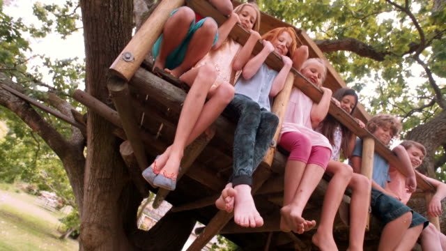 Children sitting on edge of treehouse in green leafed tree video