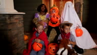 Children sitting on porch in Halloween costumes video
