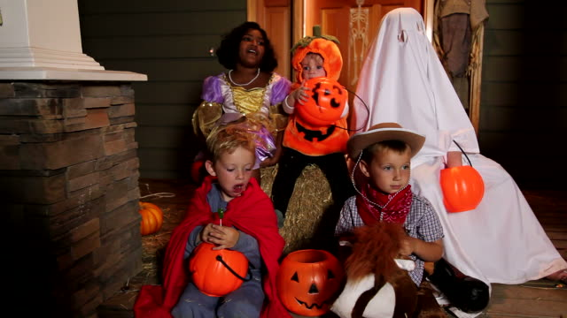 Children sitting on porch in Halloween costumes video
